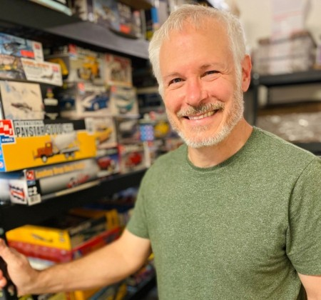Man posing in front of a shelf of toys